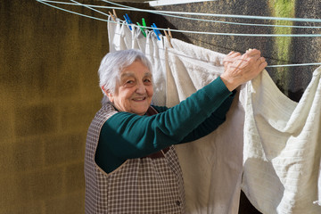 Elderly woman hanging out the washing on the terrace of her hous