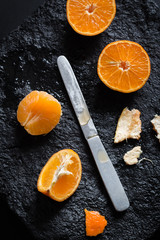 Juicy Mandarin Oranges and a Silver Knife on a Black Stone Plate