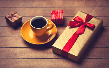 Cup of coffee and gift boxes on a wooden table.