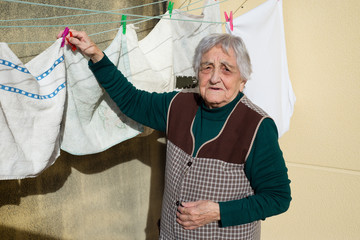 Elderly woman hanging out the washing