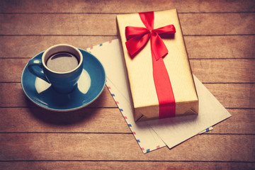 Cup of coffee and gift box with envelopes on a wooden table.