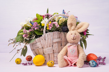 Rabbit with colorful Easter eggs and a full basket of decorative