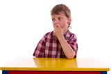 Kind am Tisch sitzend, nachdenklich