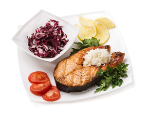 Grilled trout with vegetables and rice on a white background