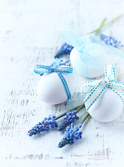 White easter eggs with ribbons and grape hyacinths