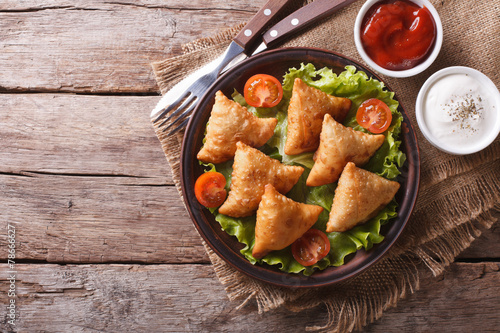 Leinwanddruck Bild samosa on a plate with sauce, horizontal top view