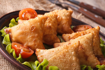 samosa with lettuce on a wooden table. horizontal closeup