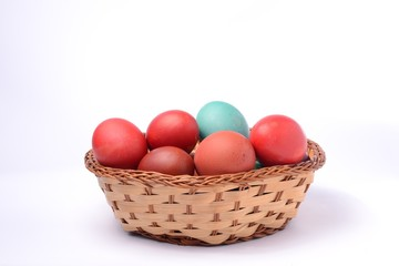 Colored easter eggs in basket. White background.