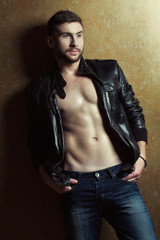 Fashion portrait of athletic young man in leather jacket
