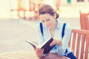 Beautiful young woman reading book outdoors.