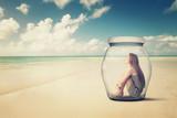 Fototapety woman sitting in jar on beach looking at the ocean view