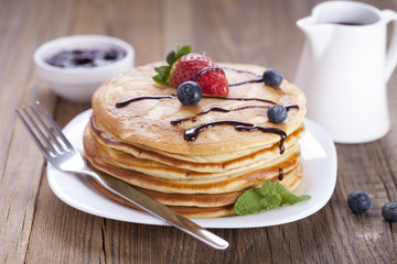 Delicious sweet American pancakes on a plate with fresh fruits