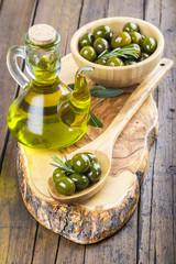 Aceitera de cristal con aceite de oliva y cuenco con aceitunas