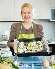 woman with fish in pan