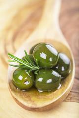 Cuchara de madera con aceitunas y aceite de oliva y romero