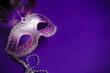 Purple Mardi-Gras or Venetian mask on purple background - 78671034