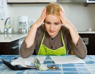 Sad woman calculating family budget