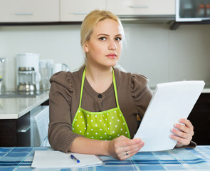 Girl reading document at kitchen