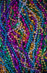 A background of  brightly colored Mardi-Gras beads