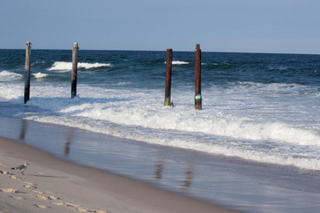Ocean waves with pilings at the beach