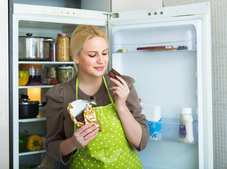 Woman eating chocolate from fridge
