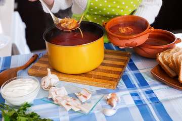 Woman pouring  Traditional Russian  soup