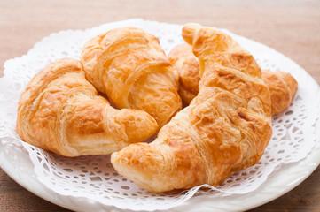 fresh croissants on wooden table