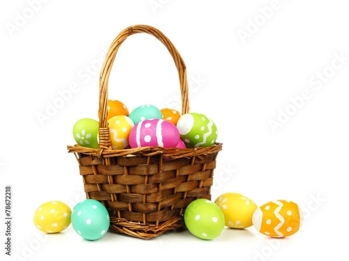 canvas print picture Easter basket filled with colorful eggs on a white background