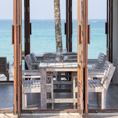 Wooden table and chairs in tropical cafe on blue sea background