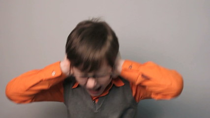 teenager boy closed his ears with his hands loud sound in