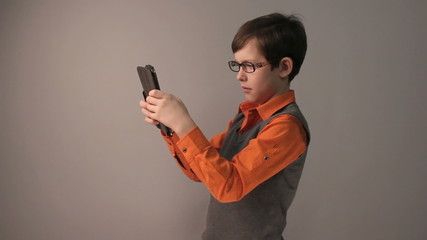 boy teenager playing tablet keen surprised in glasses gray