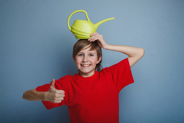 teenager boy twelve years in red shirt holding watering can