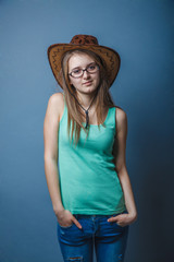 woman in blue jeans in a green T-shirt with hat looking to the s