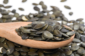 Pumpkin seed in a wooden spoon and forming a background