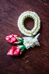 Thai traditional orchid garland on wood floor