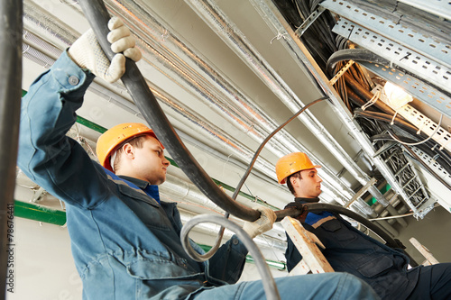 two electrician workers at cabling - 78676441