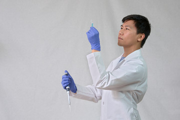 Scientist holding test tube and pipet