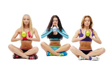 Three meditators girls holding gymnastic balls