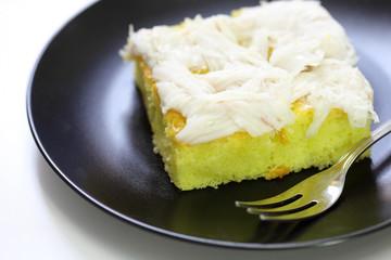 coconut cake in black plate on white background