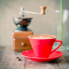 Red coffee mug , coffee grinder on wooden background.