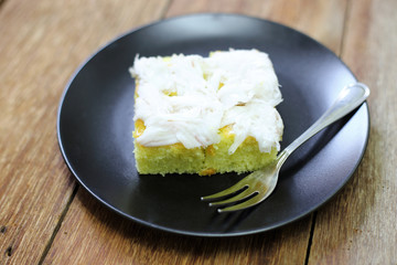 coconut cake in black plate on wood table