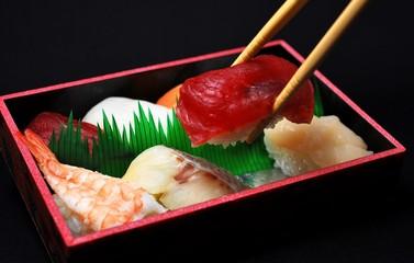 寿司弁当から箸でマグロをつまむ