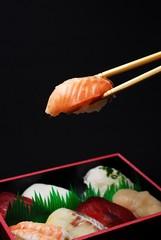 寿司弁当からサーモンを箸でつまむ