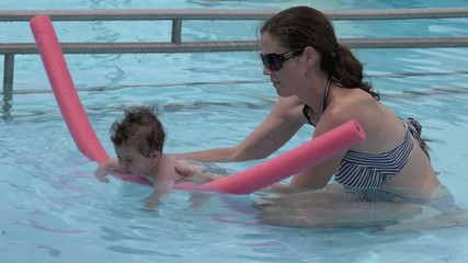 Young mother teach her baby to swiming in a swimming pool