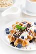 waffles with blueberries, cream and chocolate sauce, vertical