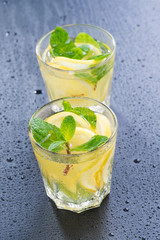 Fresh lemonade with mint in glasses on a dark background