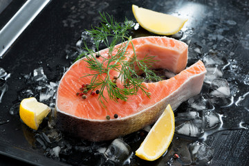 Fresh salmon steak with dill and lemon on ice