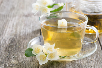 Glass cup of green tea with jasmine on wooden background