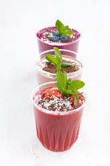 strawberry, blueberry and chocolate milkshakes in glasses