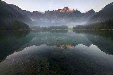 Jezioro alpejskie spowite porannymi mgłami